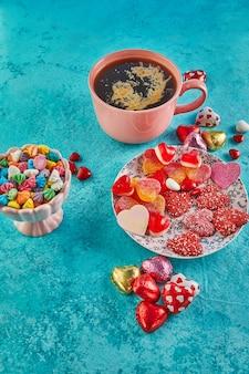 Свидание в день святого валентина с конфетными сердечками, чашкой горячего кофе и элегантной сервировкой
