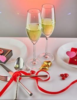 Свидание в день святого валентина с конфетными сердечками, бокалами для шампанского и элегантным столом