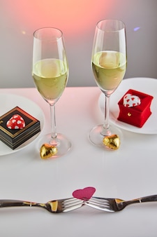 Valentine's day date with candy hearts, champagne glasses and elegant table