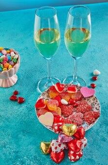 Свидание в день святого валентина с конфетными сердечками, бокалами шампанского и элегантной сервировкой