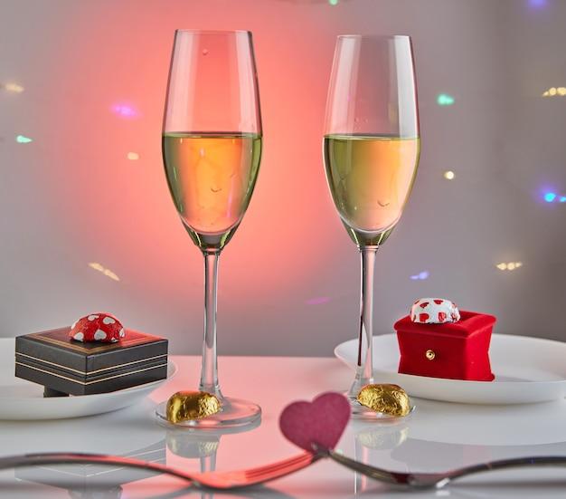 Свидание в день святого валентина с конфетными сердечками, бокалами шампанского и элегантным