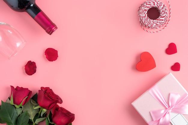 Подарок на день святого валентина с вином и розой на розовом фоне концепции дизайна