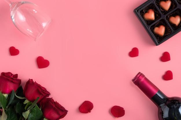 ピンクの背景デザインコンセプトにワインとバラのコンセプトとバレンタインデーのデートギフト