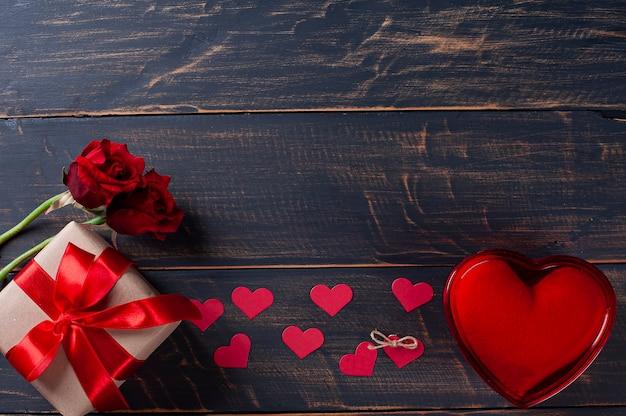 バレンタイン・デー。素朴な木製の背景にギフトボックス、赤いハートと花の装飾