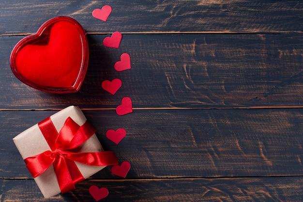 バレンタイン・デー。ギフトボックス、素朴な木製の背景に赤いハートの装飾