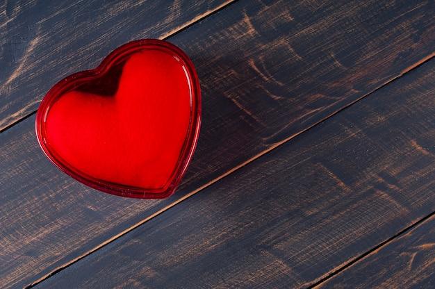 バレンタイン・デー。素朴な木製の背景に赤いハート型のギフトボックスで装飾