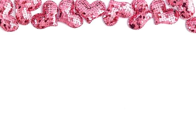 バレンタインデーの装飾的な境界線。白い背景の上の多くのピンクのスパンコールの心。