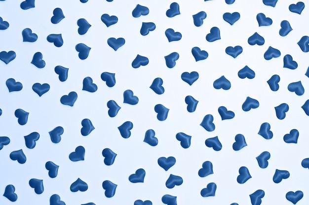 Valentine's day decorative pattern blue hearts confetti on white background.