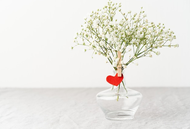 Valentine's day. delicate white flowers in vase. red felt heart - symbol of lovers