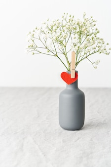 Valentine's day. delicate white flowers in a vase. red felt heart - symbol