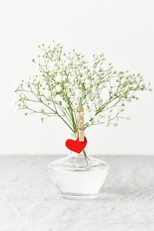 Valentine's day. delicate white flowers in vase. red felt heart - symbol