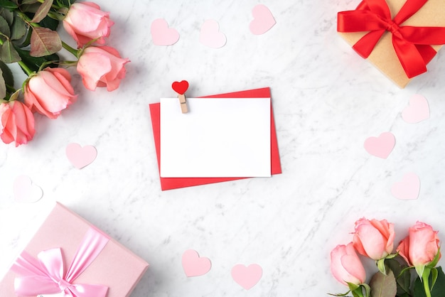 Valentine's day design concept background with pink rose flower, gift box and card on marble white background