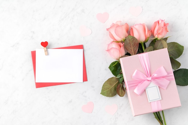 Valentine's day design concept background with pink rose flower and gift box on marble white background