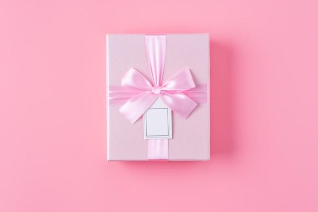 Фон концепции дизайна дня святого валентина с розовым цветком и подарочной коробкой на розовом фоне