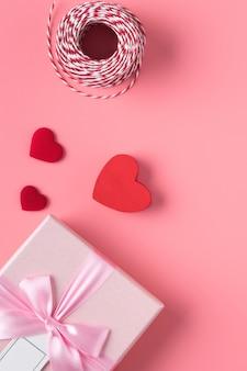 Концепция дизайна на день святого валентина с розовым цветком и подарочной коробкой на розовой поверхности