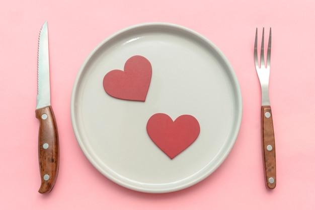 Сервировка tabble концепции обеда дня святого валентина со столовыми приборами на розовом фоне.