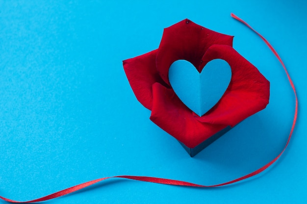 Valentine's day and eighth of march, rose petals and heart in box on blue background.