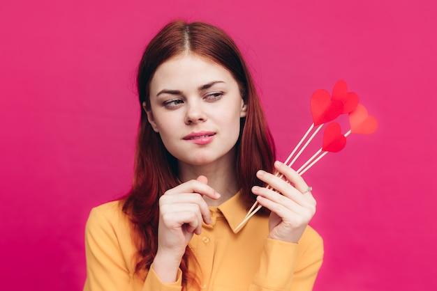 День святого валентина эмоциональная женщина с бумажными сердечками на палочке на розовом фоне и модной рубашке