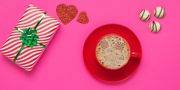 Valentine's day or the feast of saint valentine concept. gift and foam latte, red hearts and white chocolate candies. romantic pink card. a red cup and saucer with hot drink in the morning.