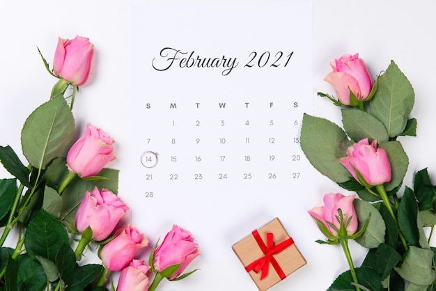 バレンタインデーの2月のカレンダー、ダイヤモンドリング、ギフト、白い背景にピンクのバラ。