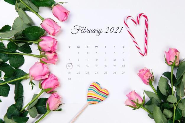 バレンタインデーの2月のカレンダー、ダイヤモンドリング、ハート、白い背景にピンクのバラ。