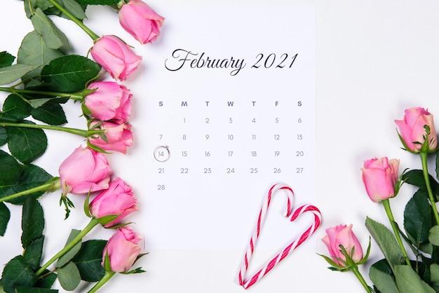 バレンタインデーの2月のカレンダー、ダイヤモンドの指輪、赤いハート、白い背景にピンクのバラ。