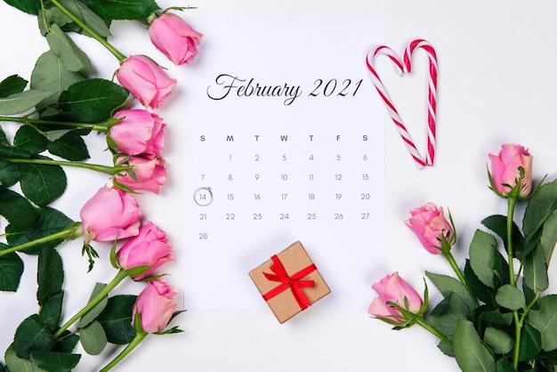 バレンタインデーの2月のカレンダー、ダイヤモンドリング、赤いハート、ギフト、白い背景にピンクのバラ。