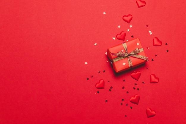 День святого валентина праздничный фон с красивым подарком, блестящей лентой и любовью формирует сердце на красном фоне.