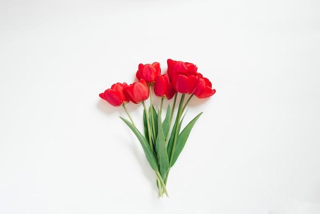 День святого валентина плоская планировка. букет красивых красных тюльпанов на белом фоне.
