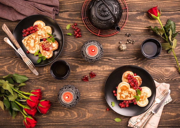 Valentine's day flat lay with delicious pancakes in form of heart, green tea, black teapot