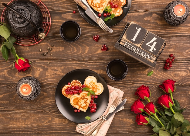 バレンタインデーのフラットは、ハート、緑茶、黒のティーポット、キャンドル、バラの形のおいしいパンケーキで横たわっていました。バレンタインデーのコンセプトグリーティングカード。上面図