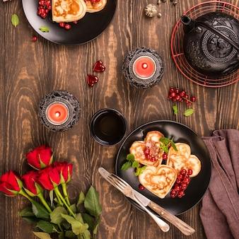 В день святого валентина лежат вкусные блины в форме сердца, зеленый чай, черный чайник, свечи и розы.