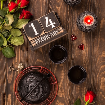 Valentine's day flat lay with green tea, black teapot, candles, roses and wooden calendar
