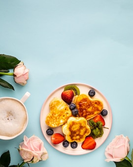 Valentine's day flat lay with heart shaped pancakes on a blue. valentine's day concept. top view. copy space. vertical