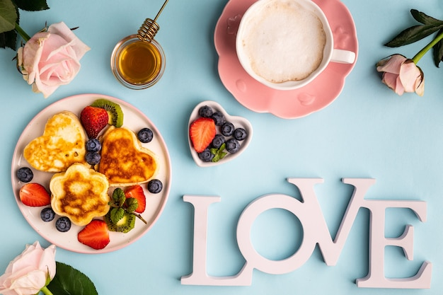 Valentine's day flat lay with heart shaped pancakes on a blue. valentine's day concept. view from above.