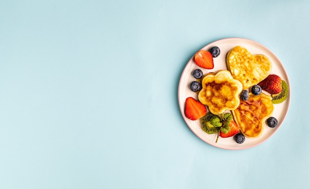 Valentine's day flat lay with heart shaped pancakes on a blue.