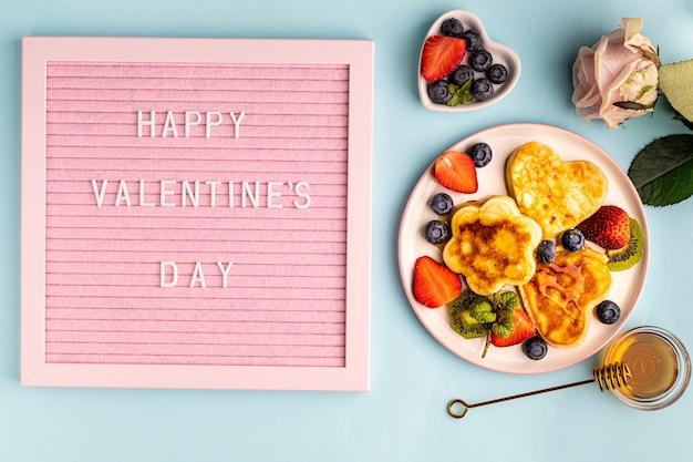 バレンタインデーのフラットは、ブルーにハート型のパンケーキを置いて横たわっていました。バレンタインデーのコンセプト。上からの眺め。