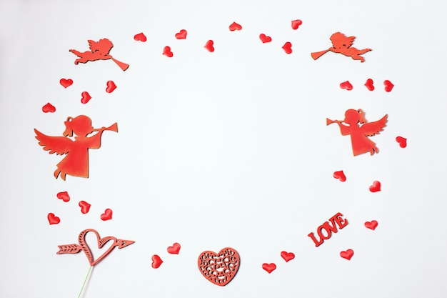 Valentine's day. frame made of gifts, heart confetti, angels on pink background. valentines day background.
