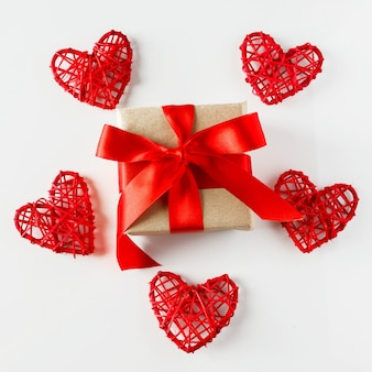 バレンタインデーの贈り物と白い背景の上の赤いハート。バレンタインデーのためのハートに囲まれた赤いリボンとクラフト紙のギフト