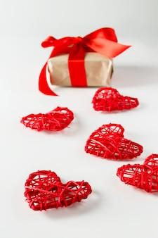 Подарок на день святого валентина и красные сердца на белом фоне. подарок ко дню всех влюбленных на фоне красных сердечек из веточек веточек, фото вертикальное