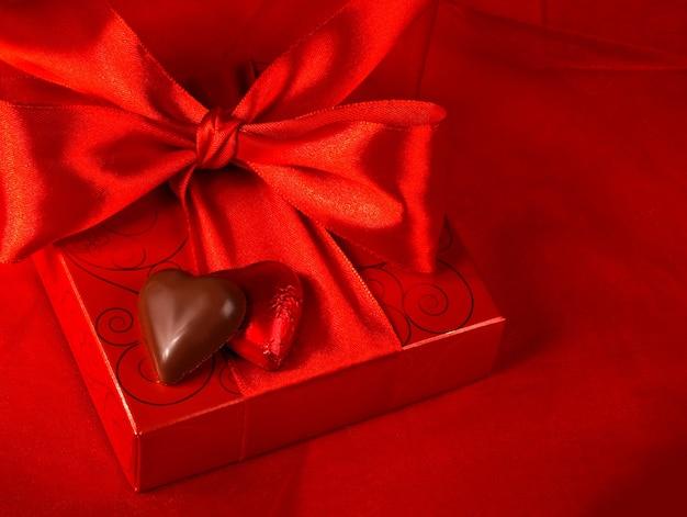 バレンタイン・デー。赤い背景にハートの形のギフトボックスとキャンディー
