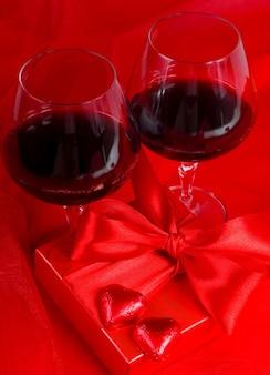 バレンタイン・デー。ギフトボックス、花、赤の背景にハートの形でワインとキャンディーとグラス