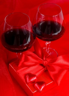 Valentine's day. gift box, flowers, glasses with wine and candy in the form of a heart on a red background