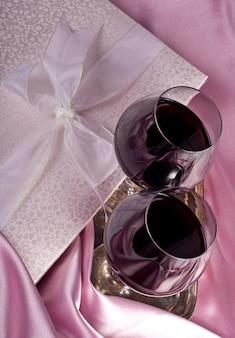 バレンタイン・デー。ギフトボックス、花、ピンク色の背景にワインとグラス