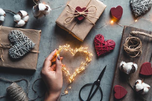 バレンタインデー、クラフト紙のギフトボックス。休日の贈り物の包装と準備。ロマンス、デート、愛