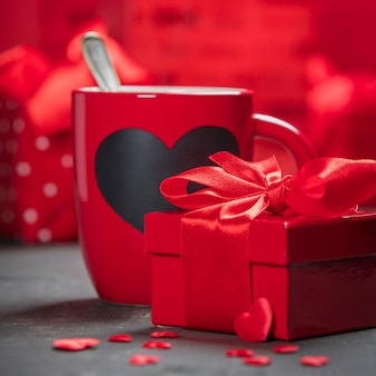 Valentine's day gift box red cups and roses on a wooden background