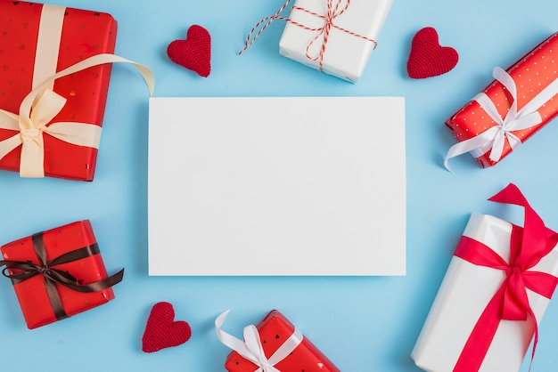 Valentine's day gift boxes and hearts around paper