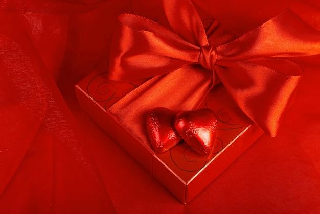 バレンタイン・デー。赤い背景にハートの形のギフトキャンディー