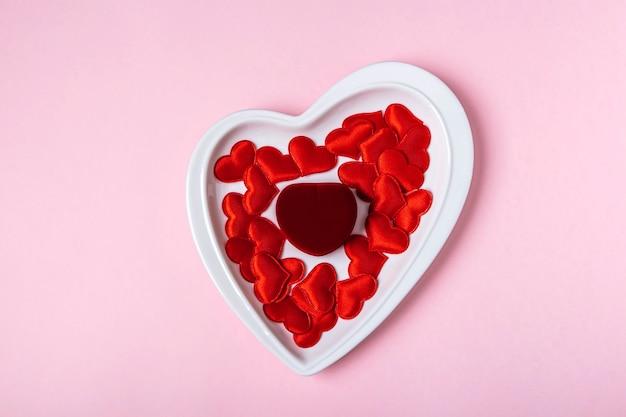 발렌타인 데이 선물. 분홍색 표면에 빨간 하트 가운데 하트 모양의 접시에 닫힌 된 보석 상자. 결혼 제안, 약혼 개념. 텍스트를위한 공간을 복사합니다.