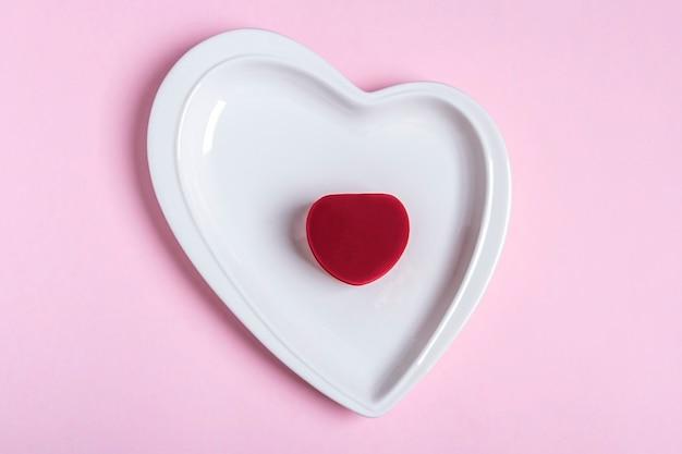 발렌타인 데이 선물. 분홍색 벽에 하트 모양의 접시에 닫힌 된 보석 상자. 결혼 제안, 약혼 개념. 텍스트를위한 공간을 복사합니다.